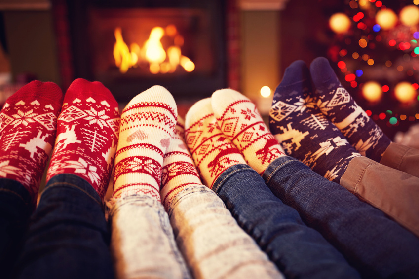 Family in socks near fireplace in winter on Christmas time